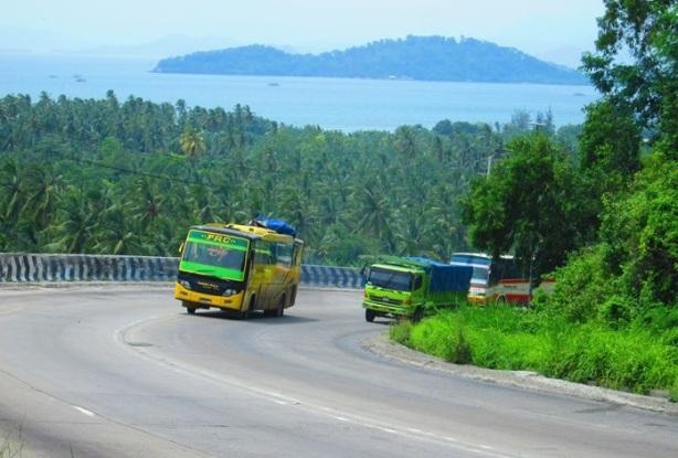 Bus Family Raya dan Lampung Jaya berusaha menyalip truk Fuso di tanjakan Tarahan, Lampung. Di kejauhan nampak panorama Selat Sunda (foto oleh Subastian Yusuf Panggabean)