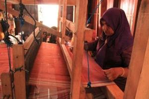 Seorang Perempuan Mengerjakan Sarung Tenun Samarinda